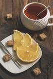 Las rebanadas del limón, amontonan el azúcar marrón y una taza de té en una tabla rústica de madera Foco selectivo entonado foto de archivo