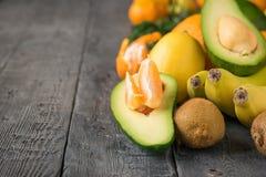 Las rebanadas del mandarín dentro del medio aguacate y de la otra fruta tropical en una tabla de madera Fotografía de archivo