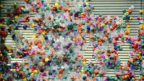 Las rebanadas plásticas coloreadas se lavaron apagado por el agua, diversidad de la tecnología, almacen de metraje de vídeo