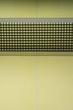 Las redes de los tenis de mesa del negro en la tabla amarilla de los tenis de mesa Imagenes de archivo
