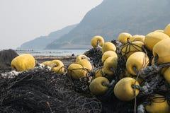 las redes de pesca negras y los japoneses amarillos de la defensa de las boyas de la pesca se abrigan Imágenes de archivo libres de regalías