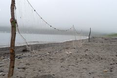 Las redes de pesca se están secando en la playa en tiempo de niebla fotos de archivo