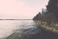 Las reflexiones en el lago tranquilo riegan con efecto del vintage del paseo marítimo Imagenes de archivo