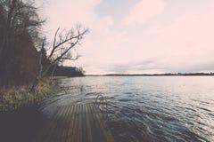 Las reflexiones en el lago tranquilo riegan con efecto del vintage del paseo marítimo Imagen de archivo libre de regalías