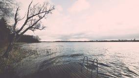 Las reflexiones en el lago tranquilo riegan con efecto del vintage del paseo marítimo Fotografía de archivo