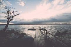 Las reflexiones en el lago tranquilo riegan con efecto del vintage del paseo marítimo Imagen de archivo