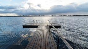 Las reflexiones en el lago tranquilo riegan con el paseo marítimo Fotografía de archivo libre de regalías