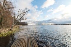 Las reflexiones en el lago tranquilo riegan con el paseo marítimo Foto de archivo
