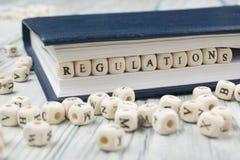 Las regulaciones redactan escrito en el bloque de madera ABC de madera Imagenes de archivo