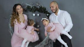 Las relaciones de familia, los padres jovenes alegres juegan con las hijas en los brazos en fondo de la pared gris con la Navidad almacen de video