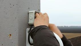 Las reparaciones de un electricista instalan un sistema de vigilancia video almacen de video