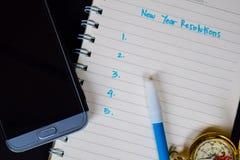 Las resoluciones del Año Nuevo mandan un SMS en el cuaderno imágenes de archivo libres de regalías