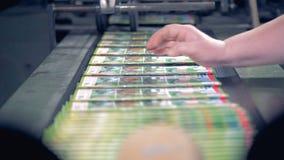 Las revistas están siendo lanzadas por una máquina tipográfica, llenadas y puestas de lado por un empleado almacen de video
