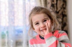 Las risas de ojos marrones de la muchacha y muerden su pulgar imagenes de archivo