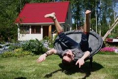 Las risas del hombre joven se sientan en una pista de la butaca encima Imagen de archivo libre de regalías