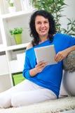 Las risas y los controles de la mujer joven en el suyo dan la tableta digital Foto de archivo libre de regalías