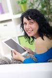 Las risas y los controles hermosos de la mujer en el suyo dan la tableta digital Fotos de archivo libres de regalías