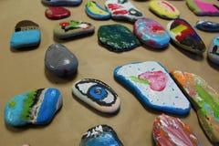 Las rocas brillantemente pintadas de los niños para un arte de la clase proyectan en la toalla de papel marrón Foto de archivo libre de regalías