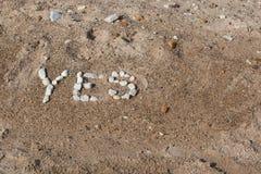 Las rocas de la playa deletrean sí Foto de archivo libre de regalías