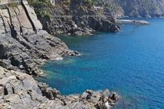 Las rocas descienden en el agua azul clara imagen de archivo libre de regalías