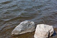 Las rocas grandes cerca de la orilla traslaparon por las ondas del lago Fotos de archivo libres de regalías