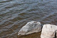 Las rocas grandes cerca de la orilla traslaparon por las ondas del lago Imagen de archivo libre de regalías