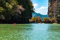 Las rocas grandes y los turistas de la piedra caliza canoeing en Phang Nga aúllan, tailandés Fotos de archivo libres de regalías