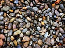 Las rocas mojadas coloridas inclinan la opinión sobre el fondo de tierra fotos de archivo