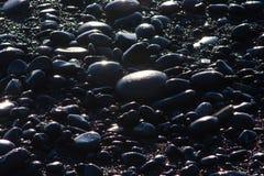 Las rocas negras relucir en el sol poniente en la playa de Rialto, Washington, los E.E.U.U. Foto de archivo