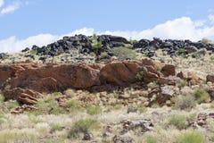 Las rocas negras y rojas en el área que confina el barranco anaranjado del río en Augrabies caen en Suráfrica Imagen de archivo libre de regalías