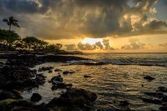Las rocas oscuras y los árboles verdes enmarcan una puesta del sol dramática en Hawaii Fotos de archivo