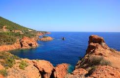 Las rocas rojas mediterráneas de Esterel costean, playa y mar Riviera francesa en Cote d Azur cerca de Raphael del santo de Canne Foto de archivo libre de regalías