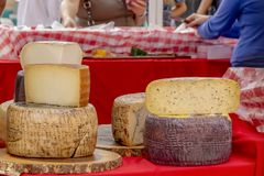 Las rondas apiladas del queso se exhiben en el mercado al aire libre de los granjeros mientras que tienda de la gente imagen de archivo libre de regalías