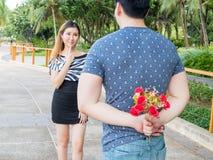 Las rosas de ocultación del hombre joven la suya parte posterior y los dan a su girlfr Fotos de archivo