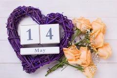 Las rosas del color del melocotón florecen, el corazón y el calendario violetas Imagenes de archivo