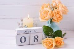 Las rosas del color del melocotón florecen, vela y calendario Fotografía de archivo