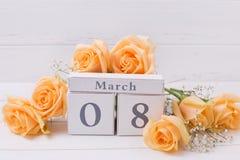Las rosas del color del melocotón florecen y calendario en los tablones de madera blancos Imágenes de archivo libres de regalías