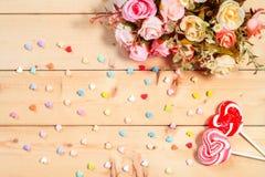 Las rosas del tono del color en colores pastel florecen con el caramelo de la forma del corazón en woode Fotos de archivo libres de regalías