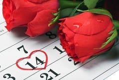 Las rosas ponen en el calendario con la fecha de la tarjeta del día de San Valentín del 14 de febrero Fotos de archivo libres de regalías