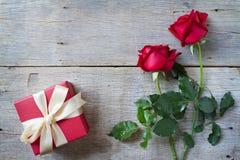 Las rosas rojas con la caja de regalo roja encendido woonden el fondo El día de tarjeta del día de San Valentín, fondo del aniver Fotos de archivo