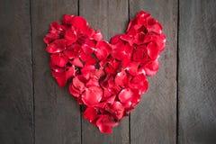 Las rosas rojas del pétalo formaron como un corazón en el fondo de madera, Foto de archivo