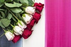 Las rosas rojas y blancas ponen completamente en fondo de madera pintado Imagenes de archivo