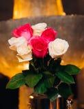 Las rosas rojas y blancas sirvieron en florero en restaurante Imagen de archivo libre de regalías