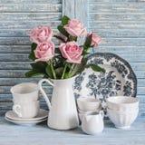 Las rosas rosadas en un blanco esmaltaron la jarra, loza del vintage en fondo rústico de madera azul Todavía de la cocina vida en foto de archivo libre de regalías