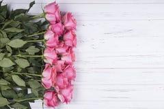 Las rosas rosadas florecen en el fondo de madera blanco con el espacio de la copia T Imagen de archivo