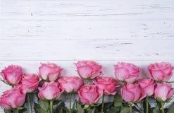 Las rosas rosadas florecen en el fondo de madera blanco con el espacio de la copia T Foto de archivo libre de regalías