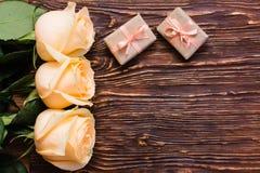 Las rosas y el regalo poner crema frescos dos embalaron en fondo de madera Imagen de archivo