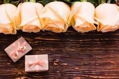 Las rosas y el regalo poner crema frescos dos embalaron en fondo de madera Fotografía de archivo