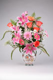 Las rosas y Lilia florece en florero en la tabla Imagen de archivo libre de regalías