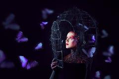 Las roturas del alma liberan de la jaula Muchacha atractiva joven en arte-maquillaje brillante, muchas mariposas fotos de archivo libres de regalías